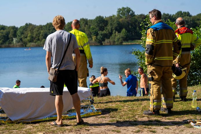 Hulpverleners en badgasten woensdag bij de Geffense Plas, waar een man van de bodem gehaald werd.