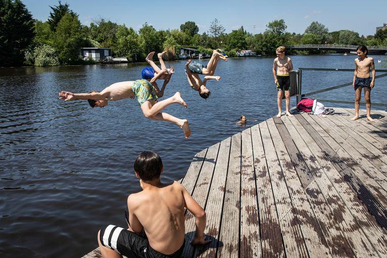 Jongens nemen een verkoelende duik in de Stadiongracht.  Beeld Dingena Mol
