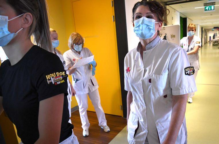 Verpleegkundigen van het Jeroen Bosch Ziekenhuis die tegen covid-19 zijn gevaccineerd laten dat op hun werkkleding zien. Beeld Marcel van den Bergh