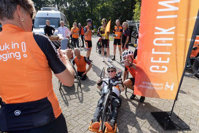 Rob Harmeling gaat bij revalidatiecentrum Libra in Blixembosch op de foto met een van de handbikers tijdens een tussenstop op hun fietsmarathon.