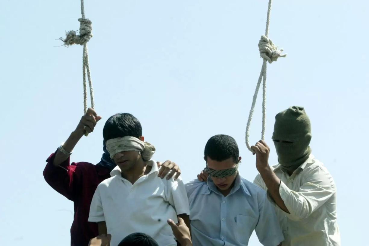 """Op 19 juli 2005 werden de homoseksuele 16-jarige Mahmoud Asgari (links) en de 18-jarige Ayaz Marhoni publiekelijk opgehangen in de Iraanse stad Mashad. Een rechtbank achtte hen schuldig aan het seksueel misbruik van een 13-jarige jongen. Volgens hun advocate legden ze de bekentenissen onder folteringen af.  Toenmalig minister van Buitenlandse Zaken Karel De Gucht (Open Vld) noemde de terechtstellingen """"barbaars."""""""