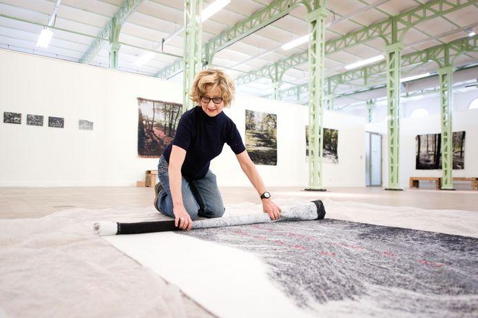 Margriet Luyten rolt een van haar wandkleden uit voor een expositie in Den Bosch in 2012.  Foto Roy Lazet