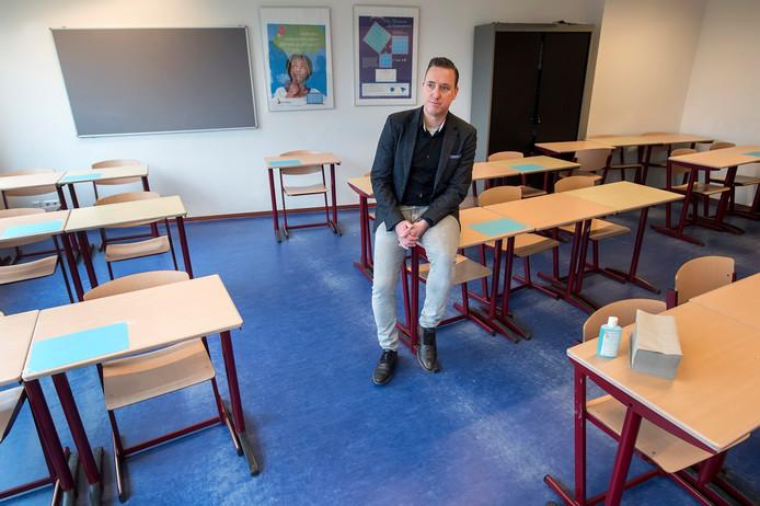 Directeur van het Markland College in een examenlokaal dat door het coronavirus de nodige aanpassingen kent. de tafels staan verder uit elkaar en zijn gemarkeerd om de zitplaatsen aan te geven. er gaan minder leerlingen in een lokaal examen doen. op de voorgrond staat desinfectiemiddel en papieren zakdoekjes.