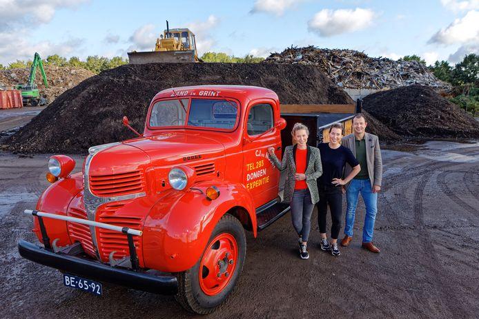Joyce, Babs en Cees van den Noort bij hun bedrijf met de rode Dodge van hun opa.