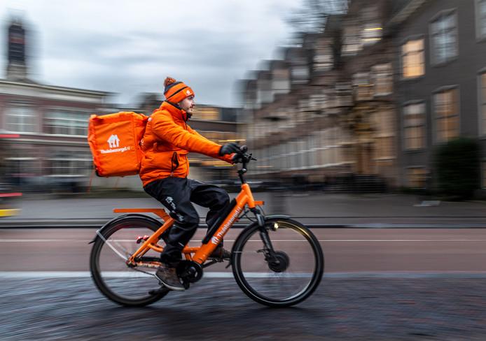 Een maaltijdbezorger op pad in Utrecht. Thuisbezorgd.nl is één van de firma's die hun bezorgers inmiddels zonder cash op pad sturen, maar veel andere bedrijven doen dat nog niet.