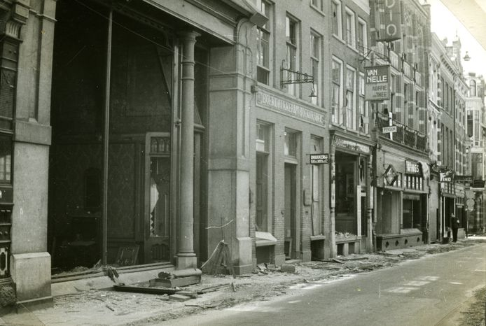 Oorlogsschade aan het St. Peters Gasthuis, mei 1945. Het pand had toen de grootste spiegelruit van de stad. Er was toen een antiekzaak in gevestigd. Bij het herstel van de oorlogsschade is de oorspronkelijke vorm van de pui weer teruggekeerd. Rechts ernaast de boekdrukkerij en boekhandel G.W. van der Wiel en Co die er in 1910 ook al zat. Daarnaast de winkel in koloniale waren en comestibles (kruidenierswaren) van F. E. van Binsbergen. Foto: Nico Kramer, Gelders Archief nr. 1523 - 148-0224, CC-BY-4.0 licentie.
