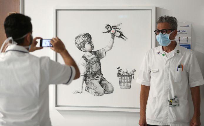 Zorgmedewerkers bij het werk 'Game Changer' van Banksy, in het Southampton General Hospital in Southampton, Engeland. Archiefbeeld.