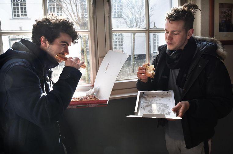 Twee studenten uit Duitsland nuttigen een pizza in de pauze Beeld Marcel van den Bergh / de Volkskrant