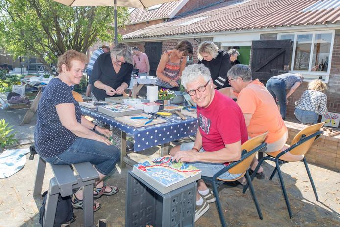 Ad Lijmbach (rood shirt) van de dorpsraad doet ook mee aan het mozaïekproject. Wethouder Marga van de Plasse (staand voor parasol) verrichte zaterdagmorgen de officiële opening en maakt zelf ook een tegel.