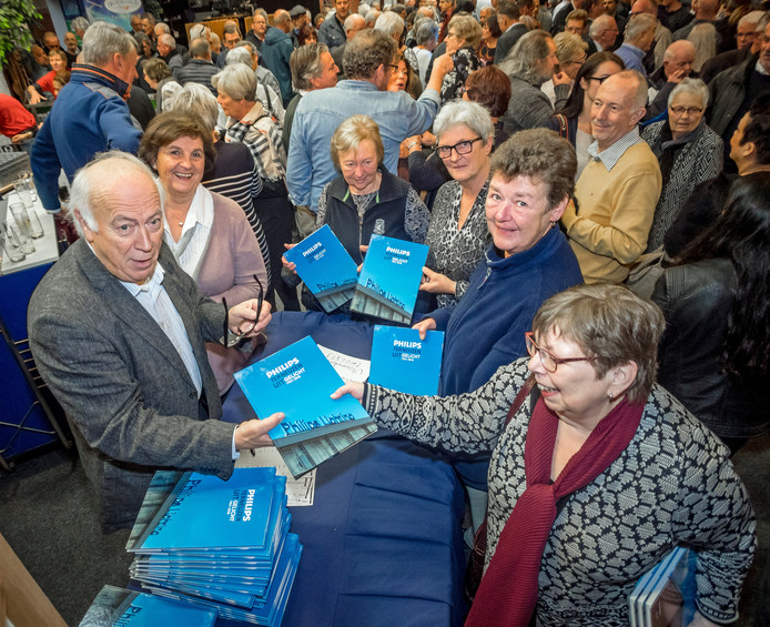 Auteur Willy Taelman (links). Zo'n 800 ex-Philips werknemers kwamen naar de Brouwzaele om een exemplaar in ontvangst te nemen.