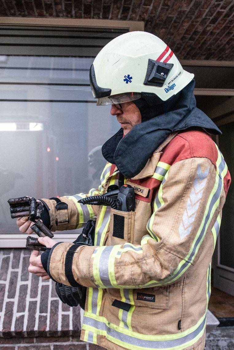 Brandweerkapitein Geert Blancke inspecteert de accu die de brand heeft veroorzaakt.