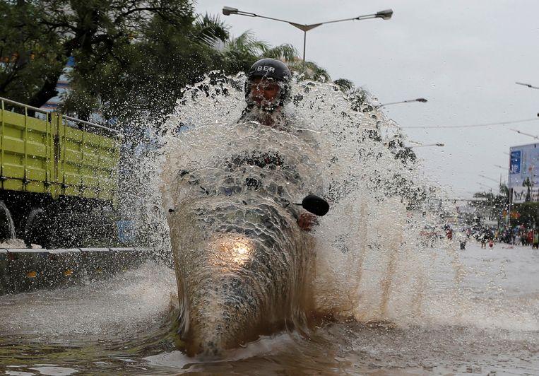 Een man op een scooter rijdt door een overstroomd gebied in Mangga Dua, Jakarta. De helft van de Indonesische stad ligt onder zeeniveau en overstroomt regelmatig. Beeld REUTERS