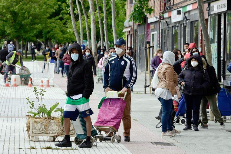 In de rij voor de voedselbank in Madrid. Door de coronacrisis vervallen steeds meer gezinnen in armoede. Beeld AFP