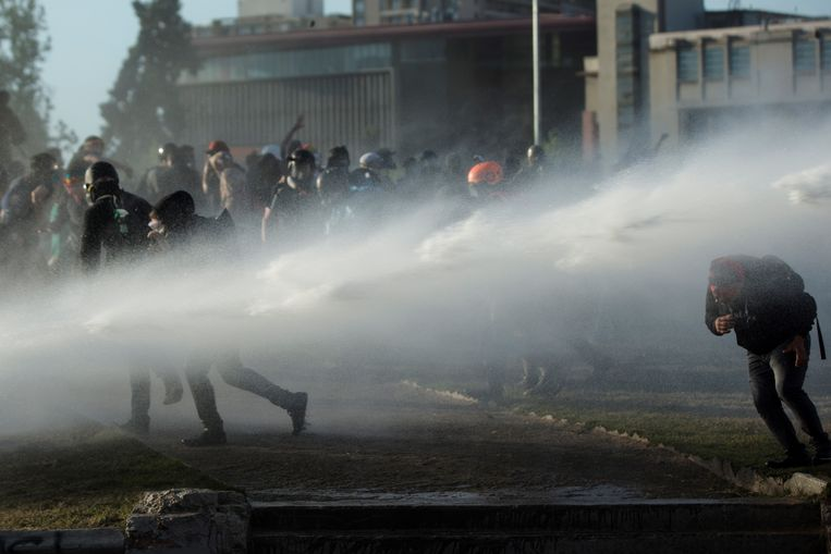 Ook tijdens het referendum raakten tientallen demonstranten in de Chileense hoofdstad Santiago slaags met de politie.  Beeld EPA