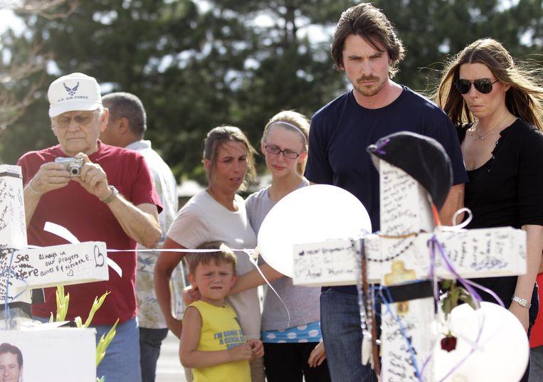 2012-07-24 AURORA - Acteur Christian Bale bezoekt samen met zijn vrouw Sandra Blazic de herdenkingsplek tegenover de Century 16-bioscoop, waar James Holmes vrijdag een bloedbad aanrichtte. De 38-jarige Bale sprak vervolgens enkele uren met zeven gewonden, hun artsen en verplegers in een ziekenhuis in Aurora. Joshua Lott/Getty Images/AFP == FOR NEWSPAPERS, INTERNET, TELCOS Beeld AFP