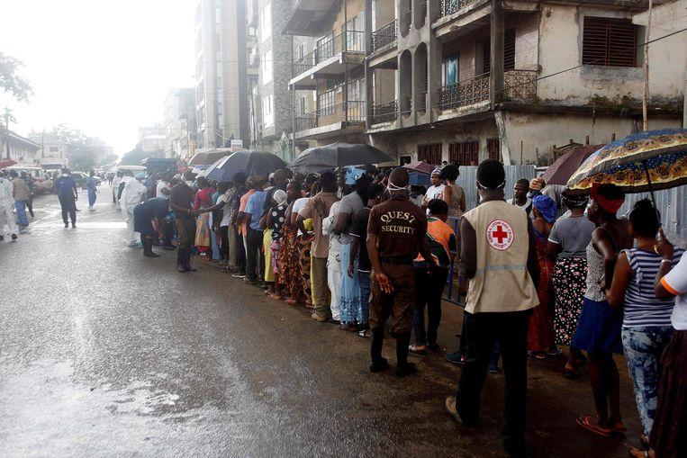Familieleden wachten buiten een ziekenhuis, hopend dat hun dierbaren de modderstroom hebben overleefd.  Beeld AFP