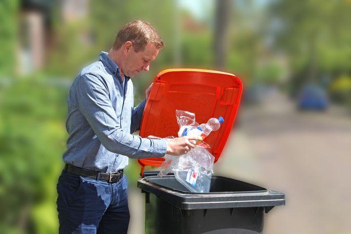 Man gooit plasticafval weg in een pmd-container.