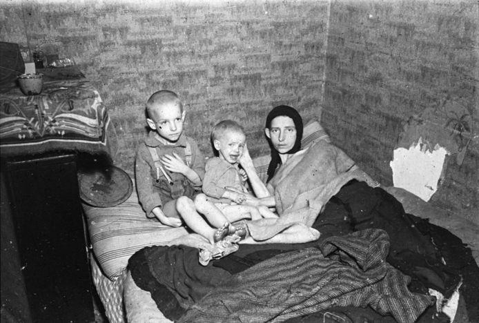 Twee uitgemergelde kinderen en hun moeder op een bed in een sterk verwaarloosd interieur tijdens de Hongerwinter, Den Haag (1944-'45)