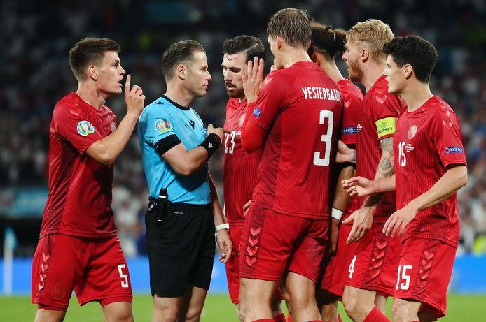 Danny Makkelie wordt belaagd door de spelers van Denemarken nadat hij Engeland een strafschop heeft gegeven.