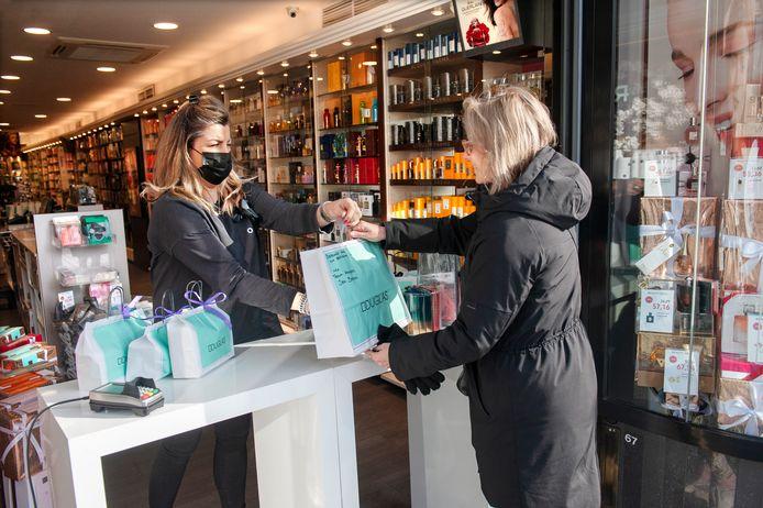 Een klant haalt haar bestelling af bij Parfumerie Douglas aan de Markt in Den Bosch. Op de foto de Click & Collect opstelling bij Douglas