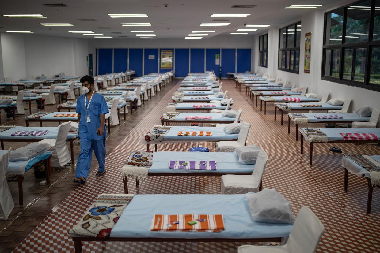Een ziekenhuismedewerker in New Delhi loopt langs de rijen bedden voor Covid-19-patiënten in een noodhospitaal. Beeld AP