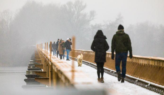 Wandelaars op de Moerputtenbrug tijdens de sneeuwval van zaterdagmiddag.