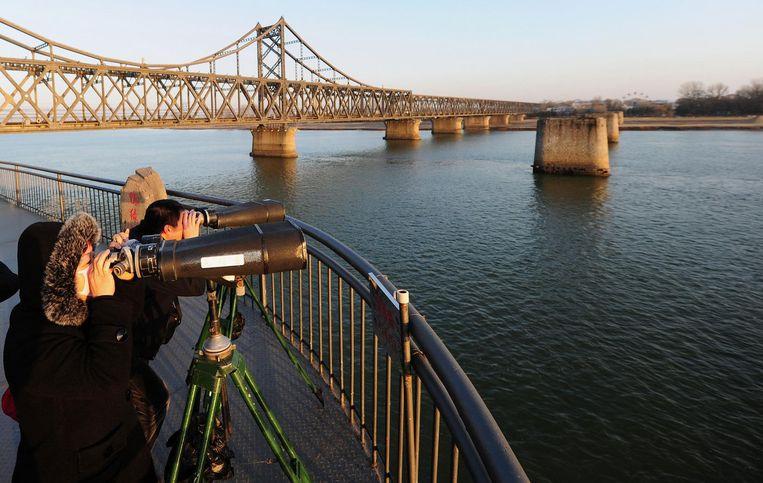 Zicht vanuit Dandong op de oude stalen brug over de Yalu naar Noord-Korea. Beeld Frederic J. Brown, AFP