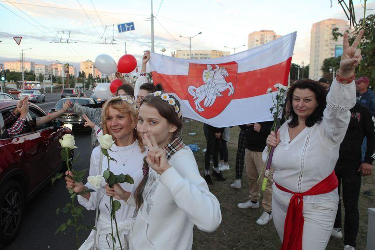 Betogers zijn op  weg om bloemen te leggen bij een herdenkingsmonument voor twee gedode demonstranten in Minsk. Beeld Maxim S