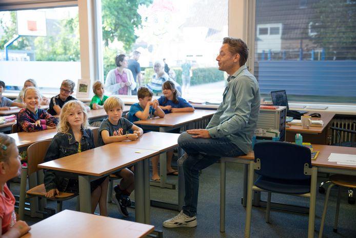 Ouders  en verzorgers staan nog even voor het raam om gedag te zeggen tegen hun kinderen, terwijl meester Tim Ravia van groep 4/5/6 de eerste schooldag inluidt op OBS de Klimop in Dreischor.