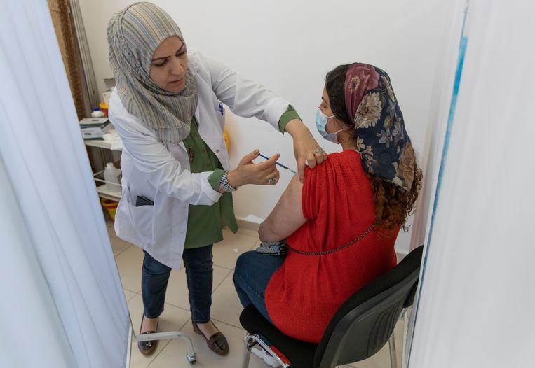 In de Palestijnse stad Ramallah, op de Westoever, krijgt een vrouw haar eerste AstraZeneca-prik. Beeld AP
