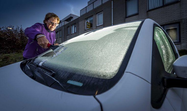 Een vrouw krabt de ruiten van haar auto.  Een ijskrabber zou altijd in de wagen moeten liggen. Beeld ANP