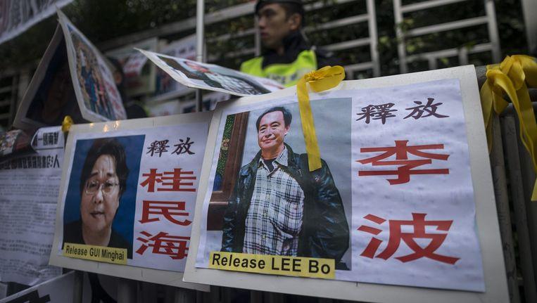 Demonstranten lopen met spandoeken van de verdwenen medewerkers van een boekhandel. Links Gui Minhai. Beeld epa