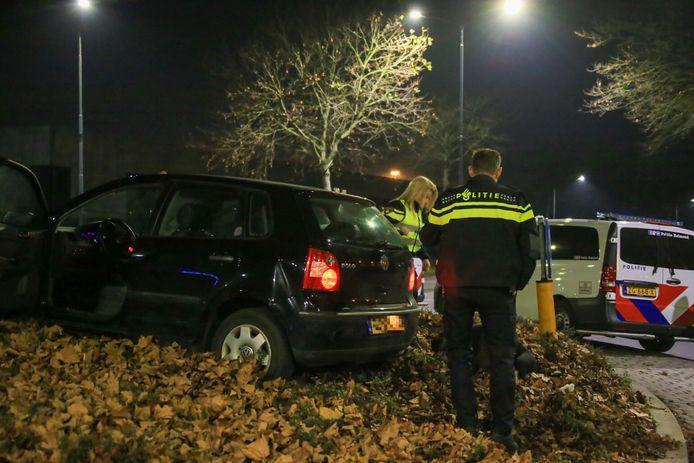 De dronken automobilist ligt op de grond, onder toezicht van agenten.