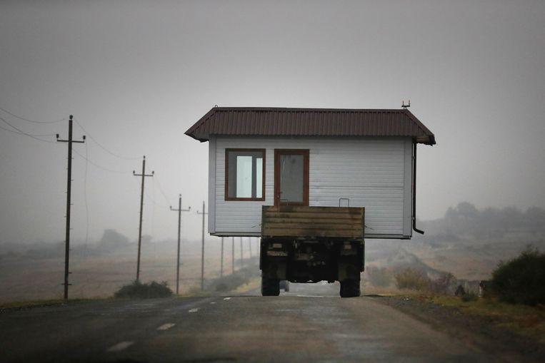 Een familie vlucht met een klein huisje uit de separatistische regio Nagorno-Karabakh.  Beeld AP