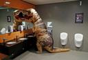 Een bezoeker verkleed als  een Tyrannosaurus Rex wast keurig na een toilet bezoek zijn handen tijdens de Comic Con in London. Foto Peter Nicholls
