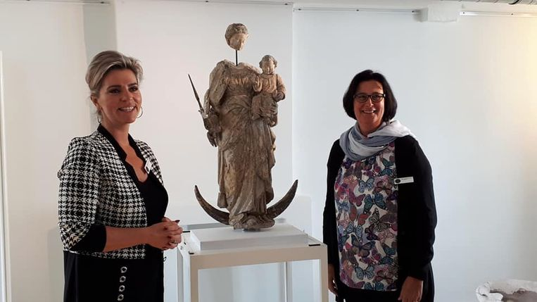 Schepenen Inge Brocken en Ingeborg De Meulemeester bij het gerestaureerde Madonnabeeld van Hof ter Welle.