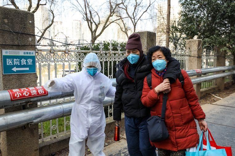 Medisch personeel buiten een ziekenhuis in Wuhan.  Beeld Barcroft Media via Getty Images