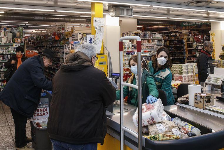 Kassiersters in een supermarkt in Rome werken met mondmaskers.  Beeld EPA