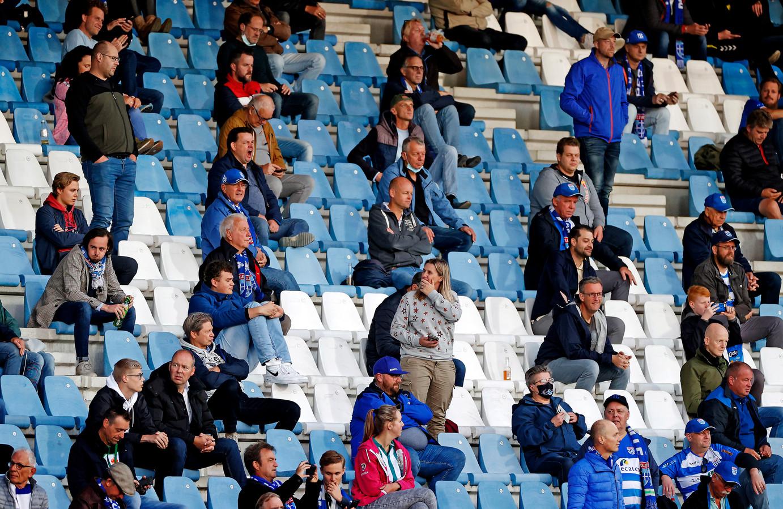 Terwijl het veld gesproeid wordt zitten de bezoekers van PEC Zwolle-Feyenoord keurig op anderhalve meter van elkaar op de tribune.