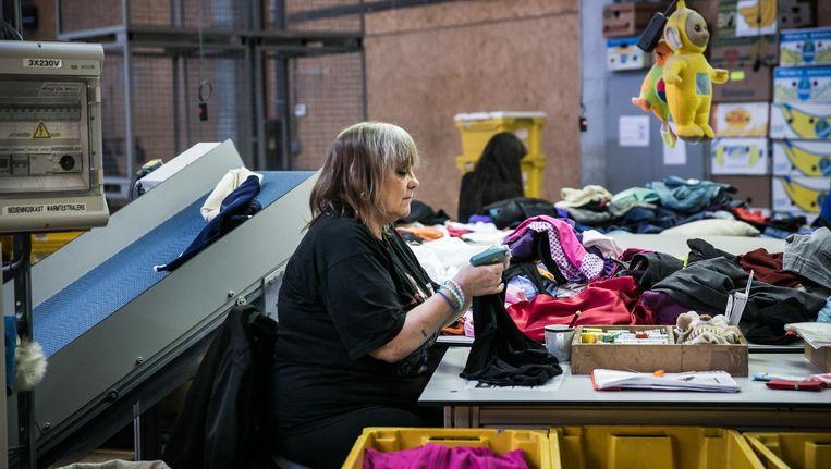 Een vrouw labelt kleren in het textielsorteercentrum van de Kringloopwinkels in Gent. Beeld bas bogaerts