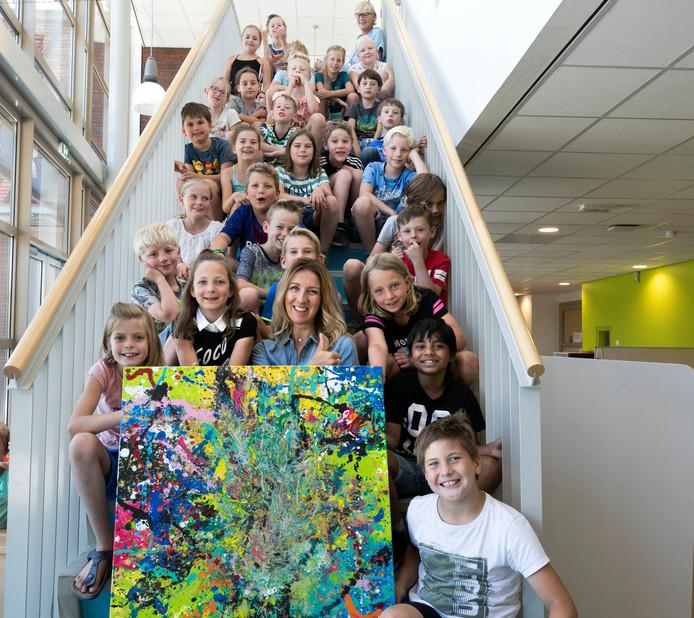 Elly Hermans samen met het kunstwerk dat door de kinderen werd gemaakt.