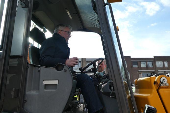 Wethouder voor even graafmachine-bestuurder op het Mercuriusplein in Berlicum.