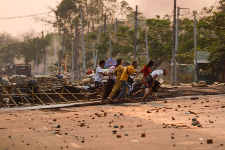Betogers rennen langs de barricades die zijn opgeworpen in Yangon.  Beeld AFP