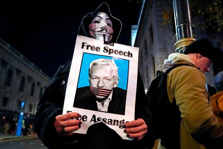Een gemaskerde betoger vraagt de vrijlating van Julian Assange.  Beeld AFP