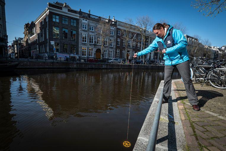 Kirsten Vendrig van Waternet meet de helderheid van het water in de Herengracht. Beeld Dingena Mol