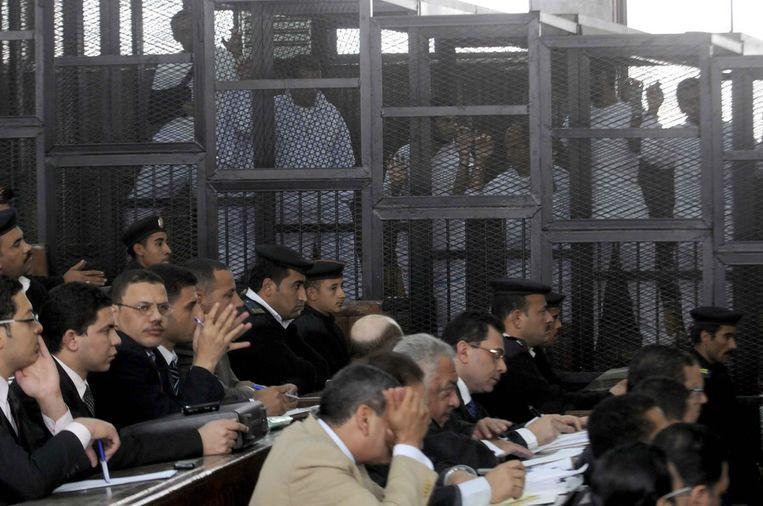Journalisten van Al Jazeera in een kooi tijdens het proces in Egypte. De journalisten worden ervan beschuldigd de Moslimbroederschap te hebben gesteund. Beeld GETTY