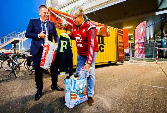 Ton Strooband, manager maatschappelijke zaken bij Feyenoord (links), aan de slag met tassen met kleding. ,,Het is toch leuk als die kinderen straks iets hebben om aan te trekken.''