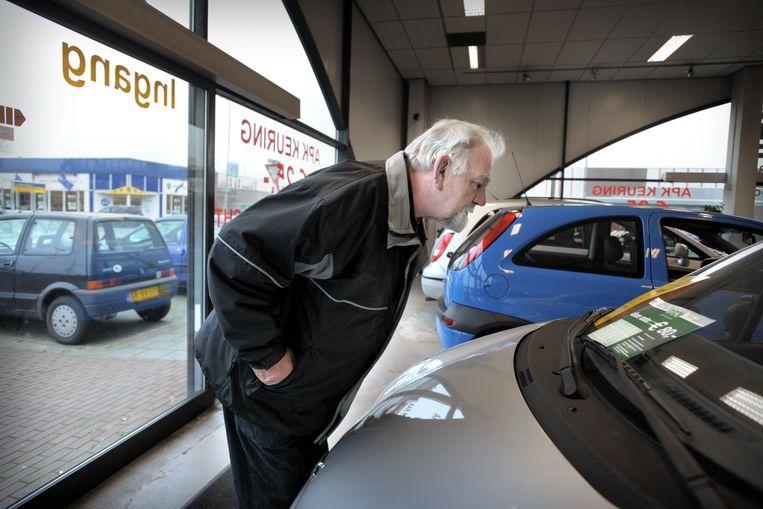 Een klant vergelijkt de prijzen in de showroom van Bovag.  Beeld Joost van den Broek / de Volkskrant