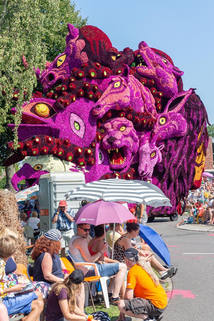 Toeschouwers wapenen zich tegen de hitte met parasols, als Twee Nijenhuizen aan komt rijden met de praalwagen Worsteling, mensen hoofd waarin allerlei duisteren gedachten rondzwerven.