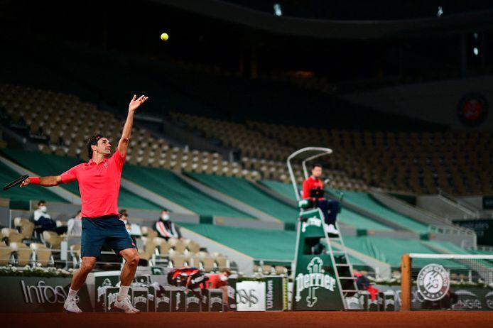 Roger Federer serveert voor lege tribunes in Parijs.